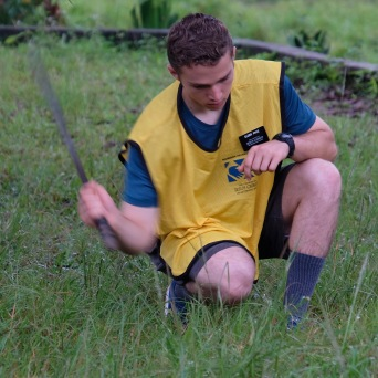 Elder Pace learning to cut weeds with a machete